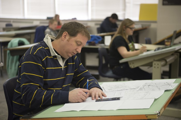Dean Tindale works on his designs in in Professor Barry Johnson's Project Coordination class