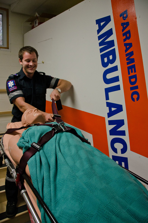 Jamie Stewart puts a test dummy into a mock ambulance during class