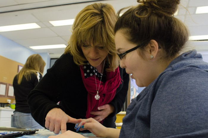 Professor Jennifer deGroot works with a student during a sensory workshop