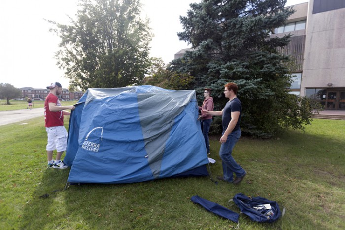 Students work together to put up a tent