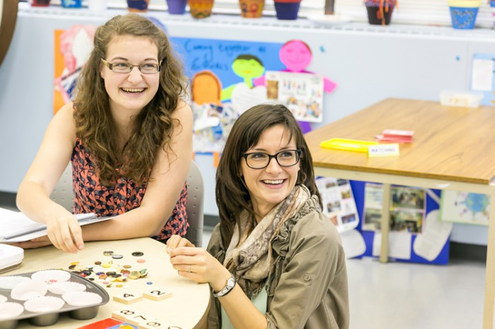 Katie Norris and Charlotte Miller set up counting and shapes activity stations in the ECE classroom