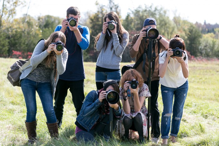 A group of students poses with their cameras