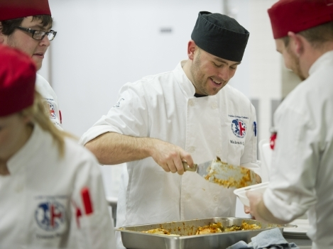 Culinary student Dave Stewart, centre, prepares lasagna at Club 213 during the fundraiser.