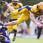 KINGSTON, Ont. (05/10/13) - Queen's University Gaels player Giovanni Aprile, 11, flies in the over Wilfrid Laurier University's Golden Hawks' Benjamin Millar, 13, during Queen's Homecoming game. Queen's Gaels had a 40-34 victory over the Wilfrid Laurier's Golden Hawks. Photo by Hannah Yoon