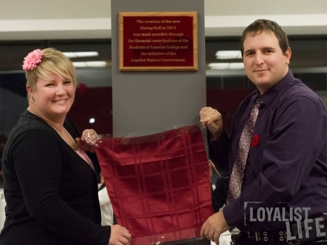 Loyalist Board of Governors Student Representative and Enactus President Elizabeth Kryschuk (left) and Student Government Past President (2012-13) Chris Detering unveil a plaque of recognition in the Dining Hall. (Photo by Carla Antonio.)